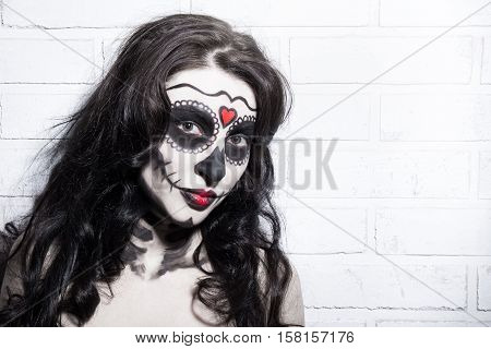 Halloween Concept - Beautiful Woman With Creative Sugar Skull Make Up Over White Brick Wall