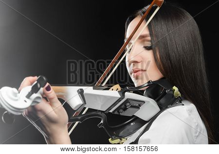 Woman playing the violin on a black background closing her eyes