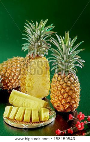 pineapple and pineapple slice on green background