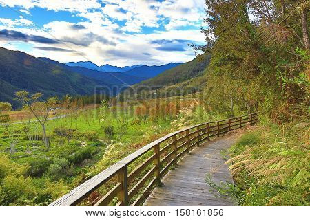 Beautiful mountain landscape with wooden hiking trail and railing in autumn