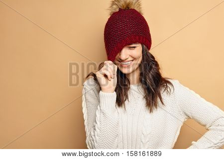 Beautiful natural looking young smiling brunette woman, wearing knitted sweater and stylish hat. Shy girl pulling her hat and laughing
