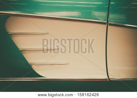 Close up shot of a vintage car's air vents on the side.