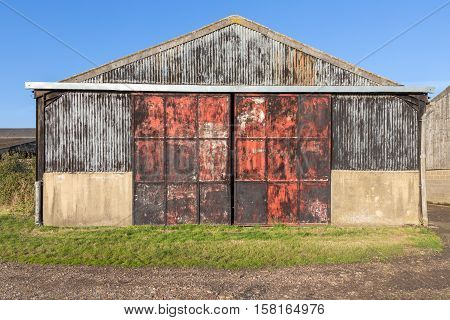 Old barn with rusty and red painted metal doors