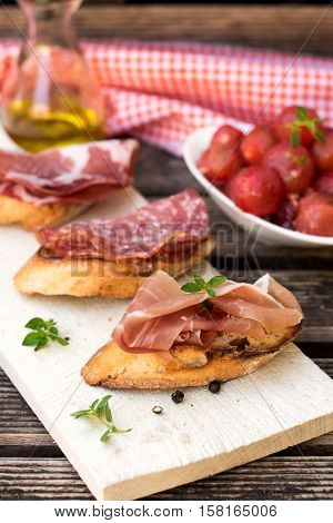 Italian ham dry cured prosciutto on bread toast with coppa and salami