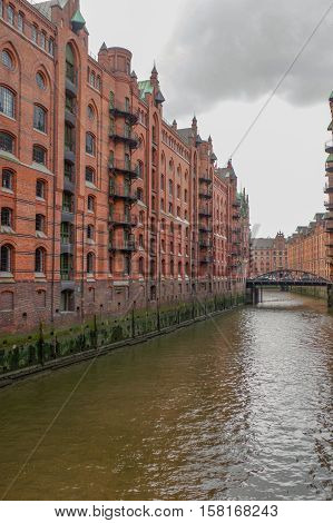 HAMBURG GERMANY - JULY 18 2015: canal of Historic Speicherstadt houses and bridges at evening with amaising skyview over warehouses famous place on Elbe river.