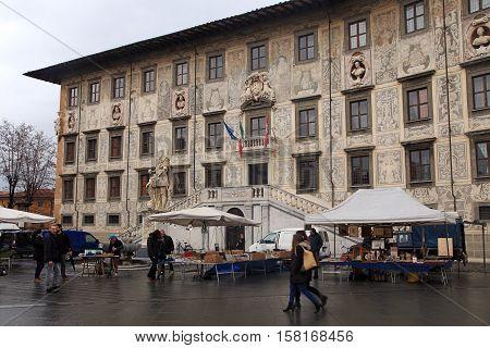 PISA, ITALY - JANUARY 9, 2016: Flea market and Palazzo della Carovana at the Piazza dei Cavalieri (Knights Square) in Pisa, Italy. The Knights Square is the second main square of the city Pisa.