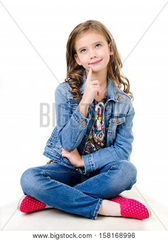 Adorable smiling little girl sitting on a floor and dreaming isolated on a white