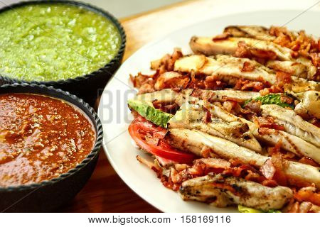 chicken fajitas on a white plate with sauces