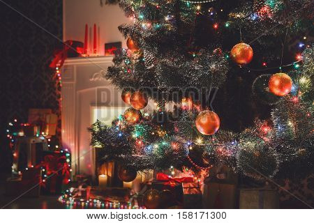 Christmas living room decorations, fireplace closeup. Beautiful xmas lights, candles, illuminated decorated christmas tree in garlands. Modern interior design, winter holidays magic night atmosphere.