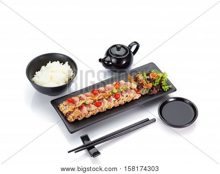 Tuna Fillet Fresh Fried With Sesame And Served On A Black Plate Isolated On White Background