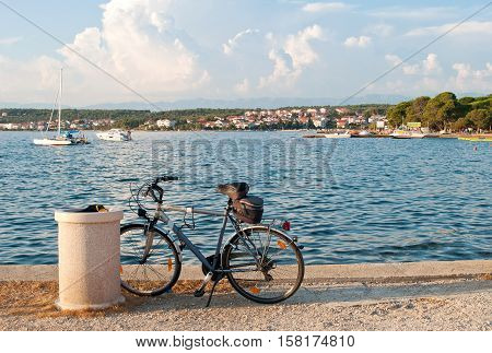 A bicycle standing near the sea against the background of the Croatian town Zadar and several motor boats sailing in the water
