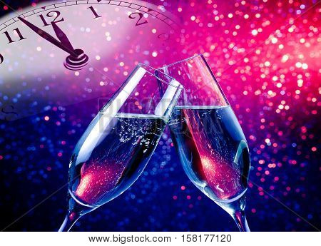 Champagne Flutes With Golden Bubbles On Blue And Purple Violet Light Bokeh Background