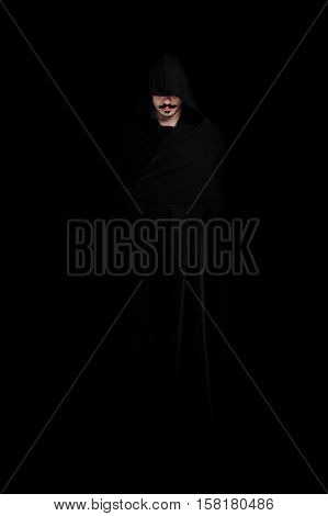 Mysterious person similar to a monk with a mustache and beard standing against a dark background in a black cloak