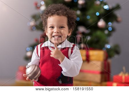 Preparing to celebrate. Adorable cute happy boy standing in front of Christmas tree and smilling while holding a Christmas decoration