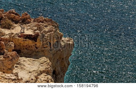 Metal chair on the high cliffs contrast with the blue ocean background.