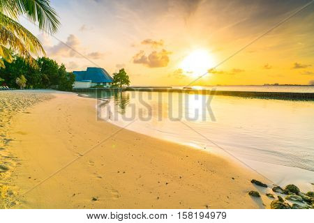 Beautiful sunrise over beach with the water villas in tropical Maldives island
