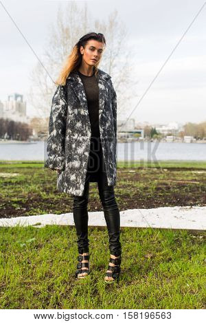 Woman in gray coat on the background of early spring grass in a park in the city. Slim model posing in a spotted coat