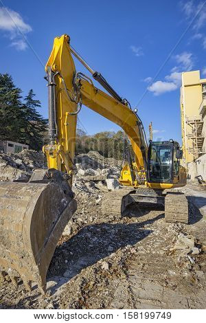 Yellow excavator with shovel at construction site .