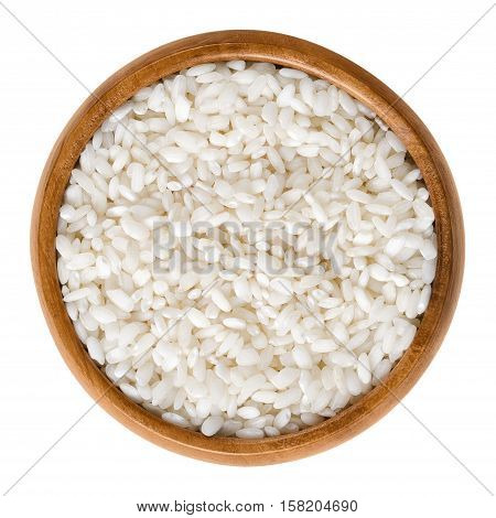 Arborio rice in wooden bowl. Italian short-grain rice with rounded grains and higher starch content, used for risotto and pudding. Isolated macro food photo close up from above on white background.