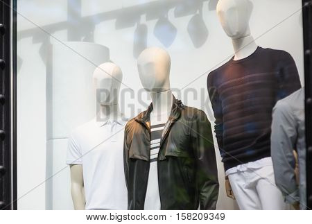 three male mannequins in the store window with clothes