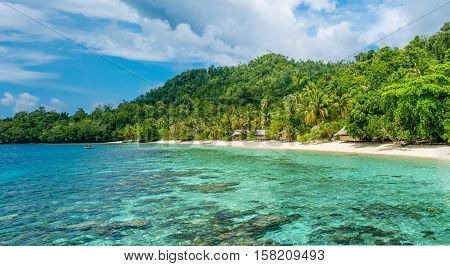 Lagoone and Bamboo Huts on the Beach, Coral Reef of Yananas Homestay Gam Island, West Papuan, Raja Ampat, Indonesia.