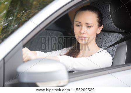 Woman buckling a seat belt in the drivers seat, safety belt, to secure against harmful movement during a collision or a sudden stop