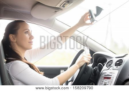 Young woman, a drowsy drive, yawning sitting at the drivers seat in the car, causing a danger of driving because of a serious lack of sleep
