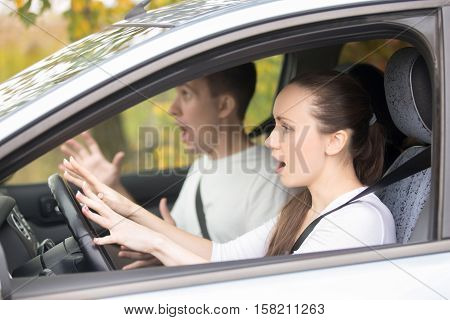 Traffic accident. Young frightened woman and a man in a car, emergency stopping, dangerous situation, driving instructor and student screaming before crash looking in windshield window