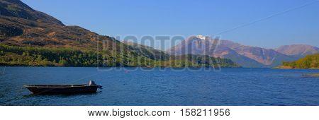 Loch Leven Lochaber Geopark Scotland uk view to Glen coe in Scottish Highlands with boat panorama