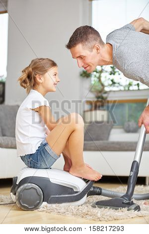 Father vacuum cleaning at home with girl sitting on vacuum cleaner