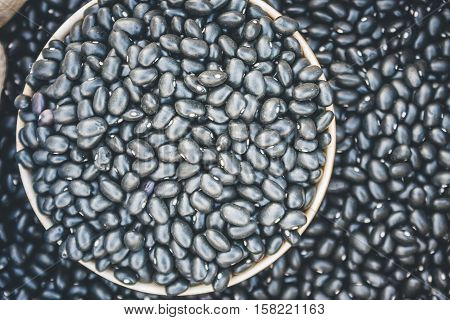 Close-Up View Of Black Beans Scattered Beans Around On A Cup With Beans Background. (View From Above)