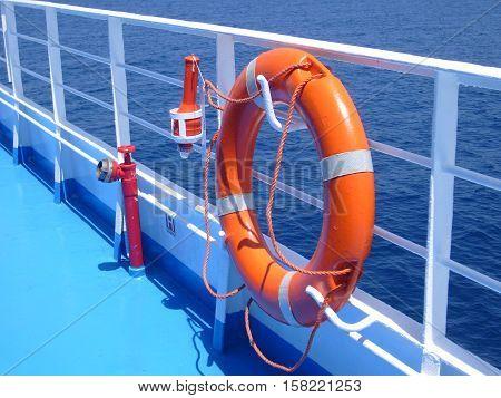 Bright orange life buoy on ferr boat in Greece
