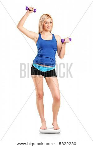 Full length portrait of a smiling female standing on a weight scale and holding a dumbbell isolated on white