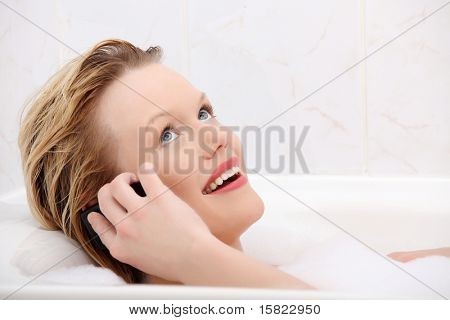 Beautiful young woman talking by mobile phone while taking a bath