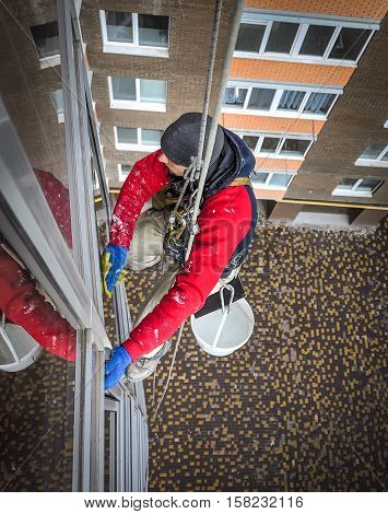 Window washer hanging on the rope gets the job done