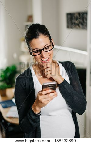 Cheerful pregnant woman texting or messaging on smartphone at home. Surprised casual female using her cellphone indoor.