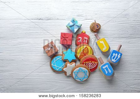 Composition of tasty cookies and dreidels for Hanukkah on light wooden table
