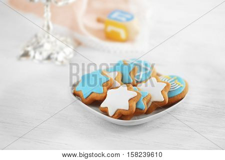 Plate with tasty glazed cookies for Hanukkah on light wooden table