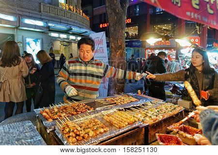 Seoul South Korea - March 14 2016: Purchase of Kebab skewers at Myeongdong open street market in Seoul South Korea