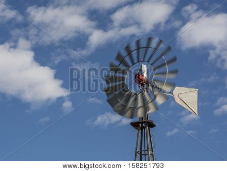 A windmill blurred by a strong wind works in an arid area of New Mexico providing a source of water for livestock.