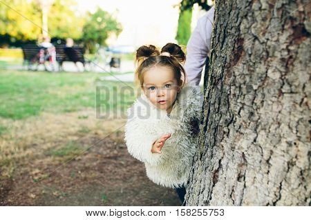 Cute little girl is playing hide and seek outdoors