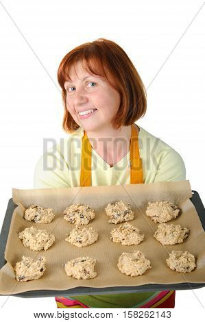 The pretty woman shows a baking cookies before put it in the oven.
