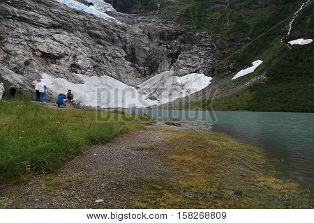 BRAEVASSHYTTA, NORWAY - JULY 4, 2016: Tourists take pictures at the foot of the glacier Suphellebreen one of the branches of a large glacier in the Jostedalsbreen National Park.