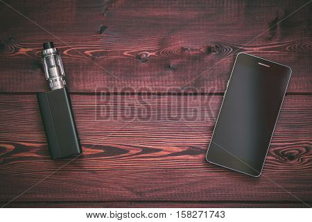 e-cig mod or electronic cigarette for vaping and smart mobile phone on a wooden background. Top view, close up