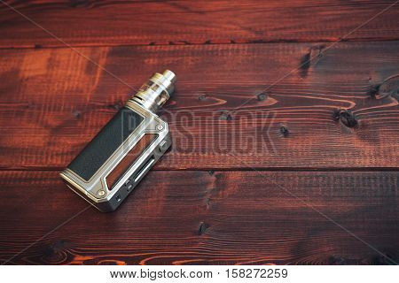 e-cig mod or electronic cigarette for vaping on a wooden background