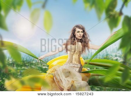 Beautiful young lady sitting on a tulip