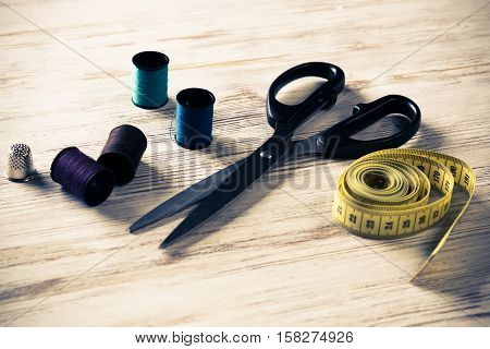 Old scissors bobbins threads and tape on wooden table