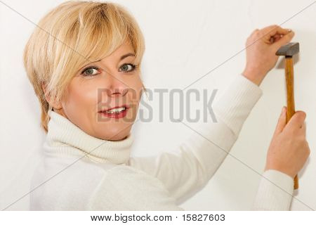 Mature woman is driving a nail into a wall in her house