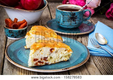 Apple cake with dried apricots on a background of old gray boards. Studio Photo
