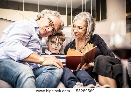 Grandparents spending time with grandson. reading him story in the living room